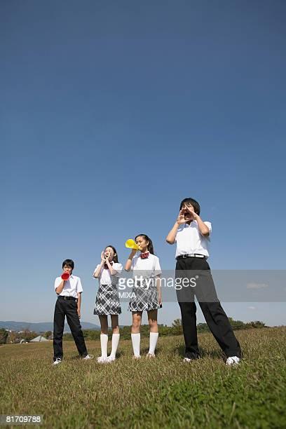 School children cheering with megaphones