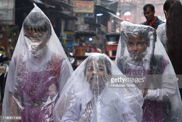 School children cover themselves with polythene sheets as they leave their school during rainfall at Jama Masjid on November 7 in New Delhi India