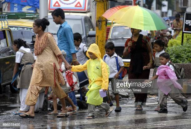 School children cross the road with their mother as it rains at Mahim Causeway