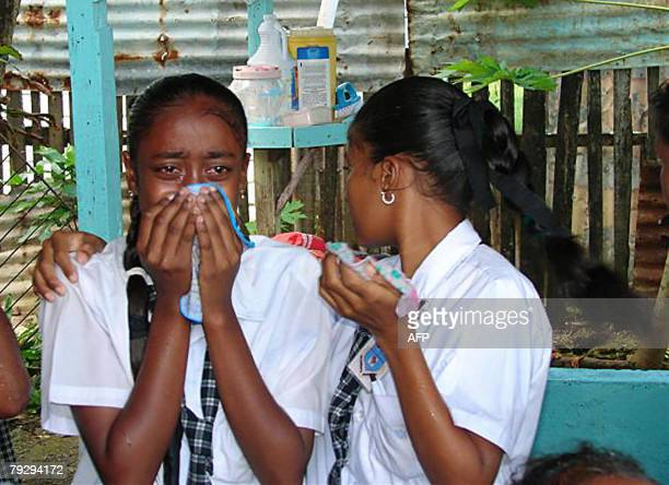 School children cry after being severely affected by teargas fired by the police at a group of protesters who were blocking the East Coast Demerara...
