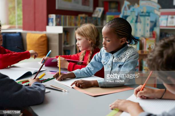 school children drawing at the school library - colouring stock pictures, royalty-free photos & images