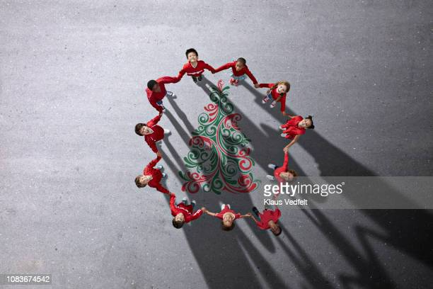 School children dressed in red holding hands, gathered around painted Christmas tree
