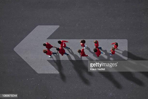 school children dressed in red, walking across big painted arrow - fortschritt stock-fotos und bilder