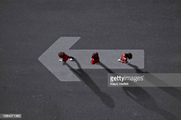 School children dressed in red, walking across big painted arrow