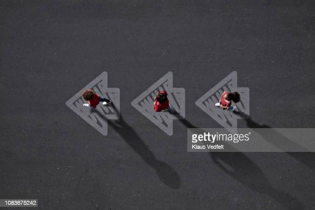 school children dressed in red, walking across painted arrows - following arrows stock pictures, royalty-free photos & images