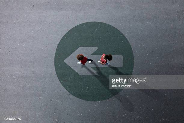 school children dressed in red, walking across painted circle with arrow - ziel stock-fotos und bilder