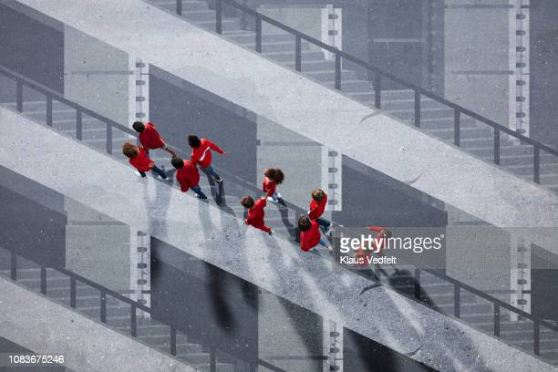 School children dressed in red, walking across painted staircase