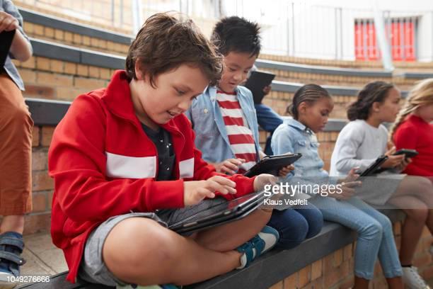 school children having class outside with digital tablets - 男子生徒 ストックフォトと画像