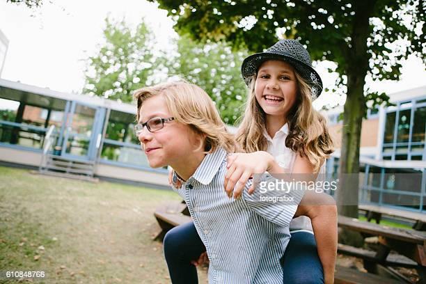 school children having fun with piggyback in schoolyard