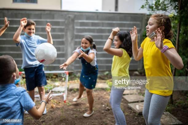 crianças de escola se divertindo com bola de futebol no quintal da escola - passe de bola - fotografias e filmes do acervo