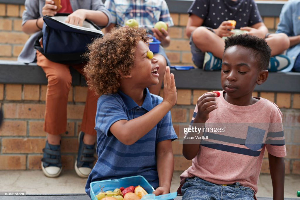 School children having lunch together outside the building : Stock Photo