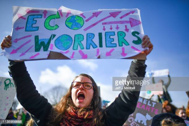School children hold placards and shout slogans as they participate in a protest outside the Scottish Parliament on March 15 2019 in Edinburgh...