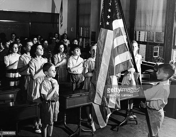 School children hold their hands across their chests while pledging allegiance to the US flag in a classroom 1950s