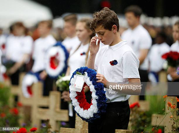 School children hold wreaths during the 100th anniversary of the beginning of the Battle of the Somme at the Thiepval memorial to the Missing on July...