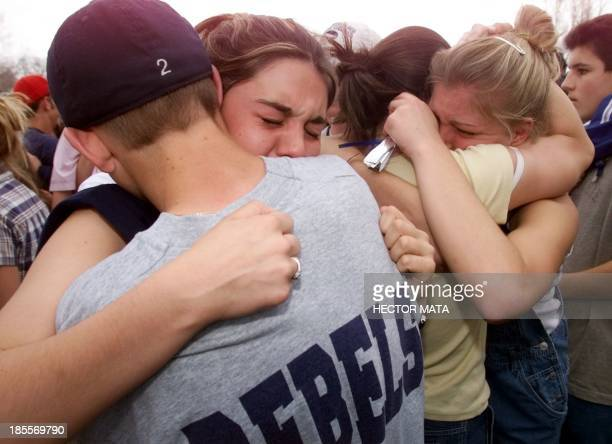School children hug each other in the parking lot 21 April 1999 outside Columbine High School in Littleton CO the site of a school shooting on 20...