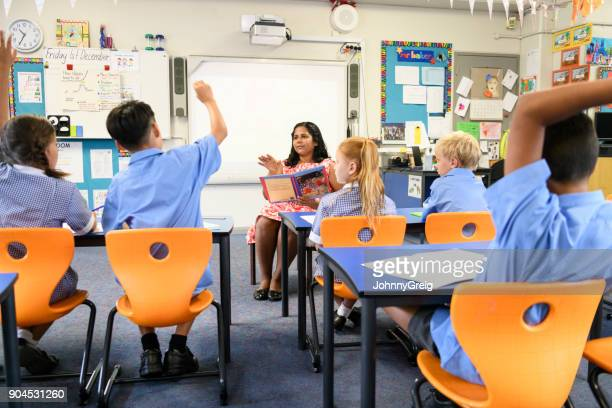 school children in classroom listening to teacher - showing respect stock pictures, royalty-free photos & images