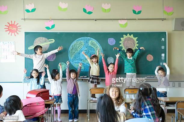 School children in classroom, raising arms