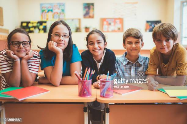 school children in the classroom smiling to camera - workbook stock photos and pictures