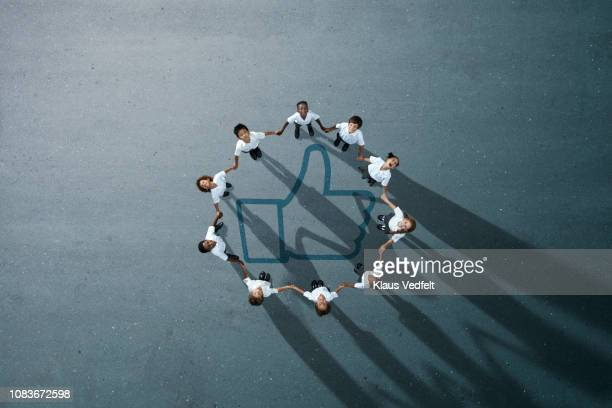 school children in uniforms standing in circle & holding hands - people icons stock pictures, royalty-free photos & images