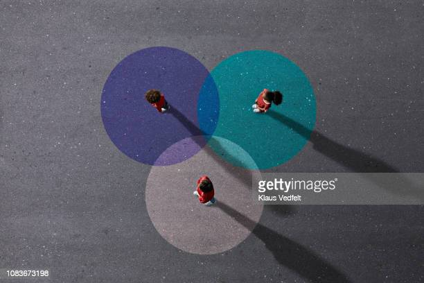 school children in uniforms standing on painted venn diagrams - three people ストックフォトと画像