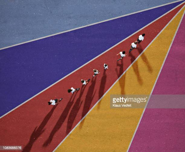 School children in uniforms walking in row on multi coloured background
