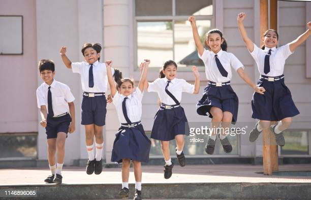 school children jumping and celebrating in school campus - indian culture stock pictures, royalty-free photos & images