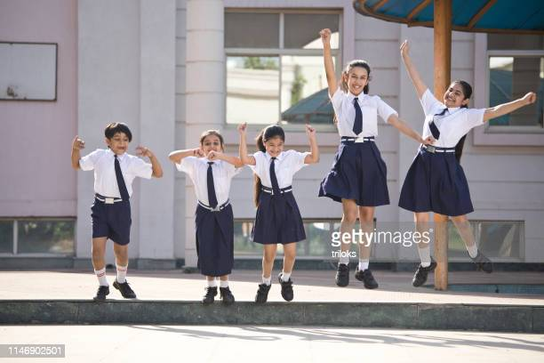 school children jumping and celebrating in school campus - first day of summer stock pictures, royalty-free photos & images