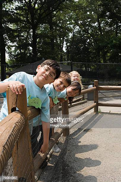 School children leaning on fence