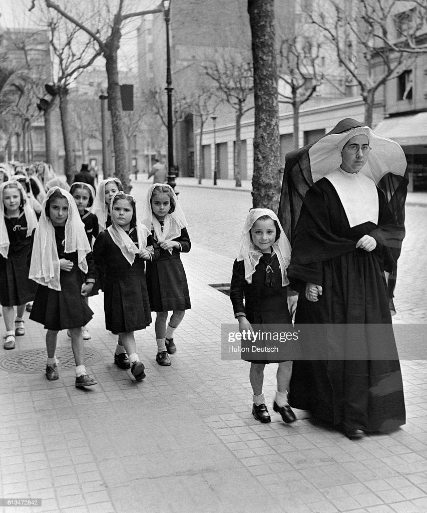 Nun Leads Children to School : News Photo