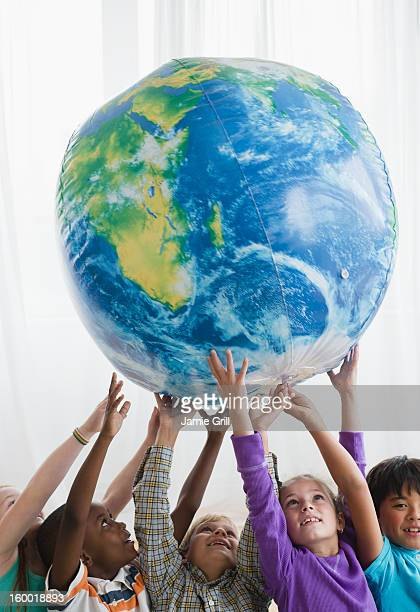 School children (8-9) lifting inflatable globe