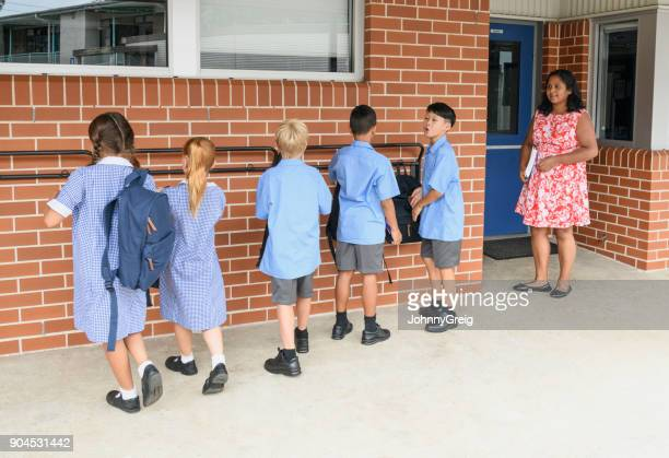 School children lining up outside school with their teacher