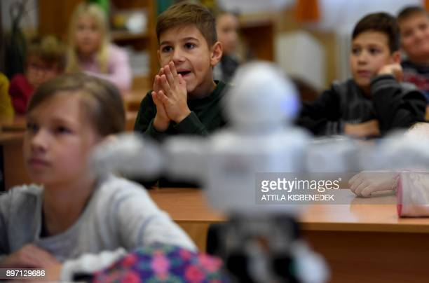 School children listen to a presentation about the internet security given by 'Robi the robot' in their classroom of a primary school in Szolnok...