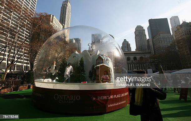 School children look at actors enclosed in a giant snow globe as part of a promotion campaign for the Canadian province of Ontario in New York 14...