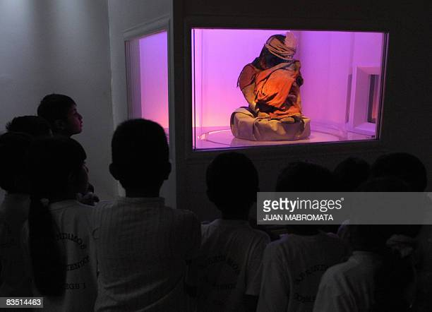 School children look at the mummy El Niño a sevenyear old Inca child found along two other frozen mummies on March 15 1999 at an altitude of 6730...