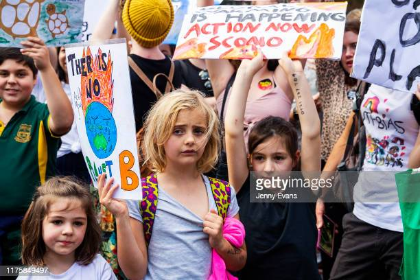 School children look on as they hold up banners outside Parliament House during a climate strike rally on September 20, 2019 in Sydney, Australia....