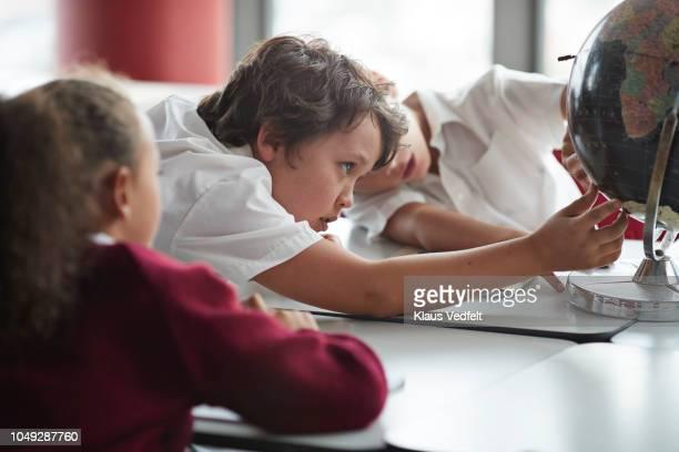 School children looking at globe in classroom