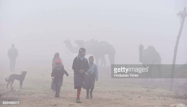 School children on their way to school on a cold foggy morning on February 1 2017 in New Delhi India Delhi recorded its lowest temperature of the...