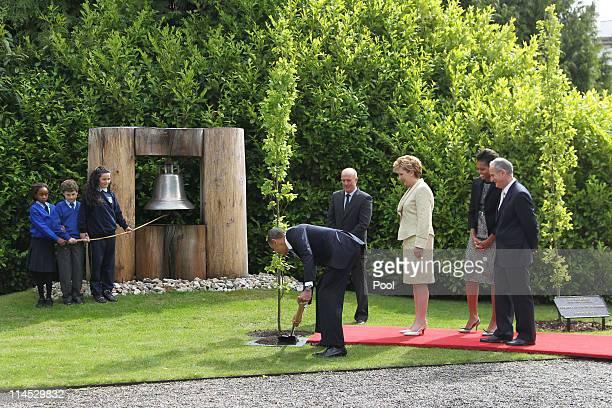 School children Onyedika Ukachukwu, Colm Dunne and Maragaret McDonagh hold the rope to the Peace Bell as U.S. President Barack Obama plants a tree...