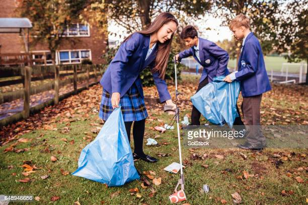 Niños recogiendo basura en su escuela