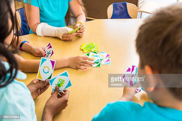 School children playing card game