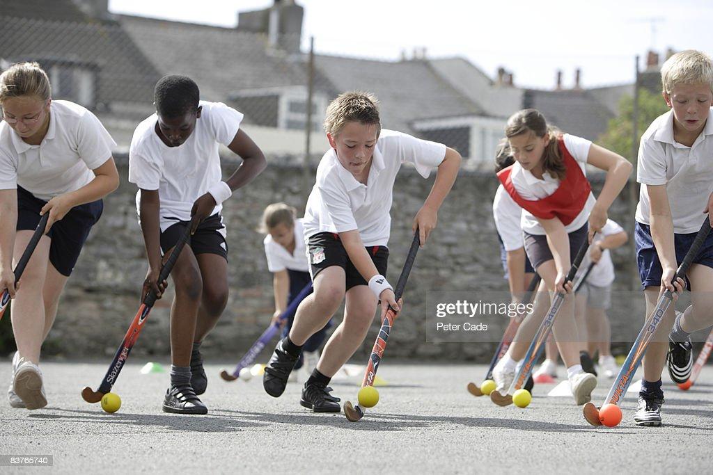 school children playing hockey : Stock Photo