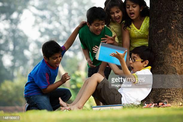 School children (6-7, 8-9) playing in park