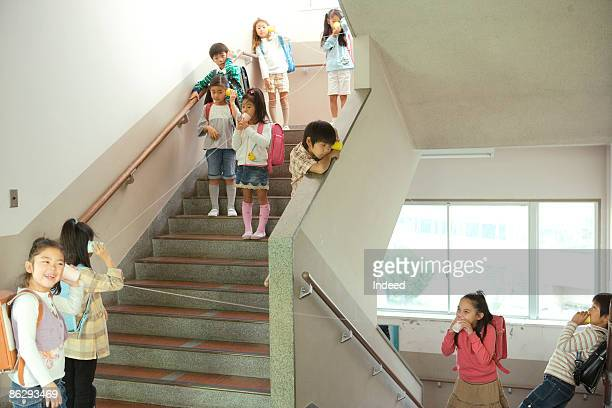 School children playing with cup phones in stair