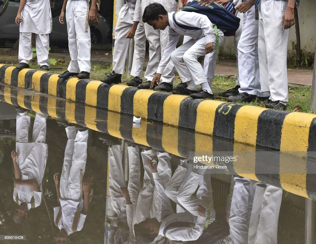 School children playing with paper boat on a waterlogged road after heavy rain at Halli Road, on August 19, 2017 in New Delhi, India. Delhi received showers early morning which brought temperatures down to a comfortable 26 degrees Celsius. The India Meteorological Department (Met) officials said that there might be thunderstorm with showers later in the day while the maximum temperature is likely to be around 34 degrees Celsius.