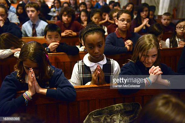 School children pray while attending noon Mass at St. Mary of the Assumption Church March 12, 2013 in Brookline, Massachusetts. The school children...