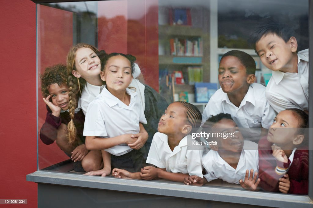 School children pressing their faces against the window in the library : Stock Photo