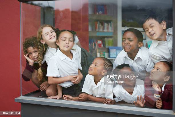 School children pressing their faces against the window in the library