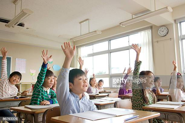 school children raising arms in class - primary school child stock pictures, royalty-free photos & images