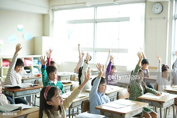 school children (6-11) raising hands - 手を挙げる ストックフォトと画像
