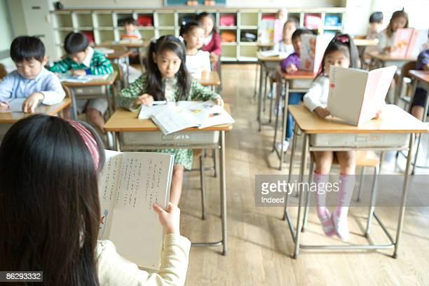 School children reading textbook in classroom